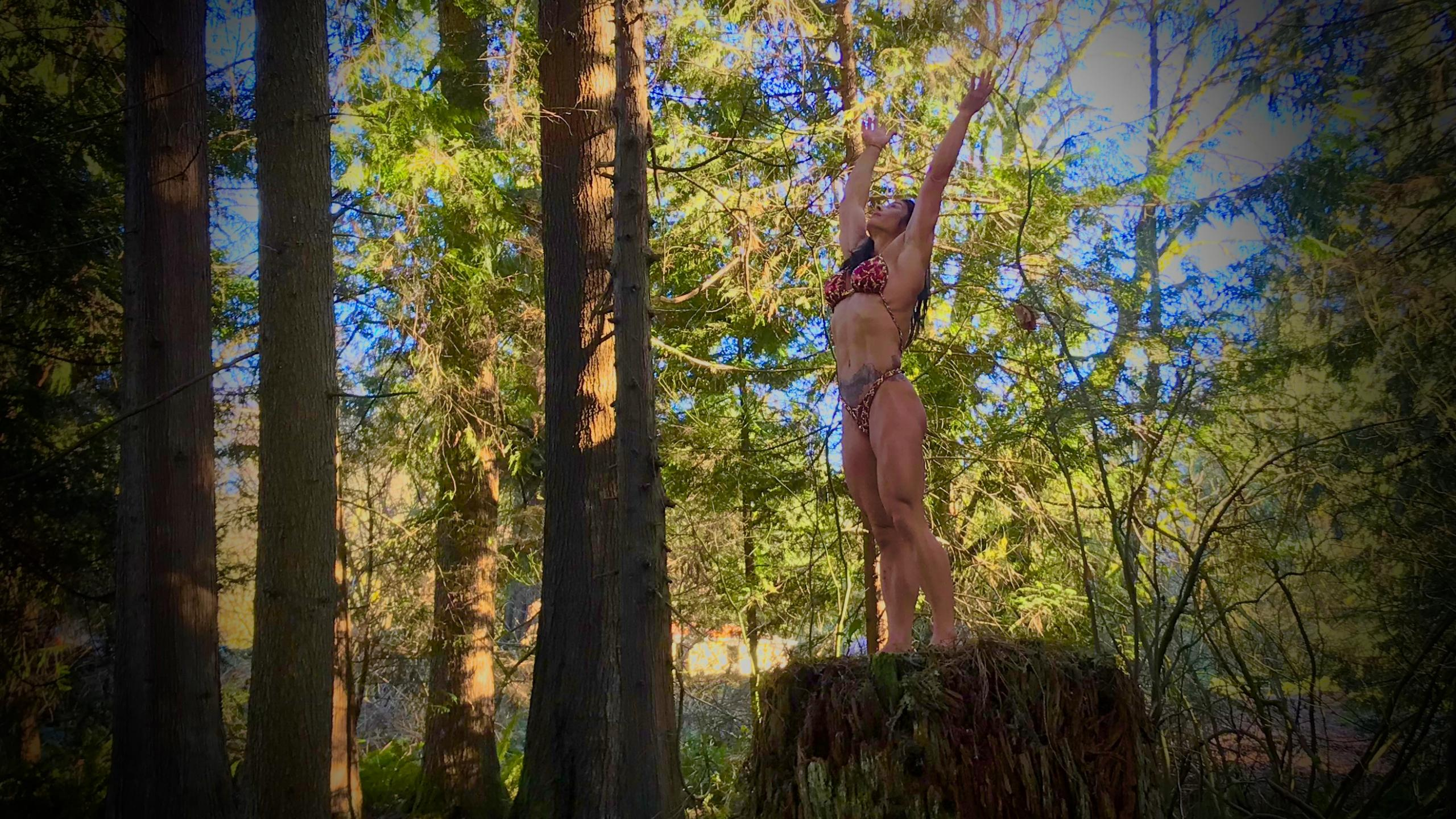 Patti Hansen on a tree stump in a Merry Christine Bodywear couture physique competition posing suit