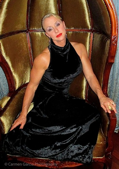 Woman in a black dress sitting in a gold velvet chair
